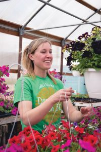 Lindsey Knoebel inspecting plants in Jelli's market greenhouse.